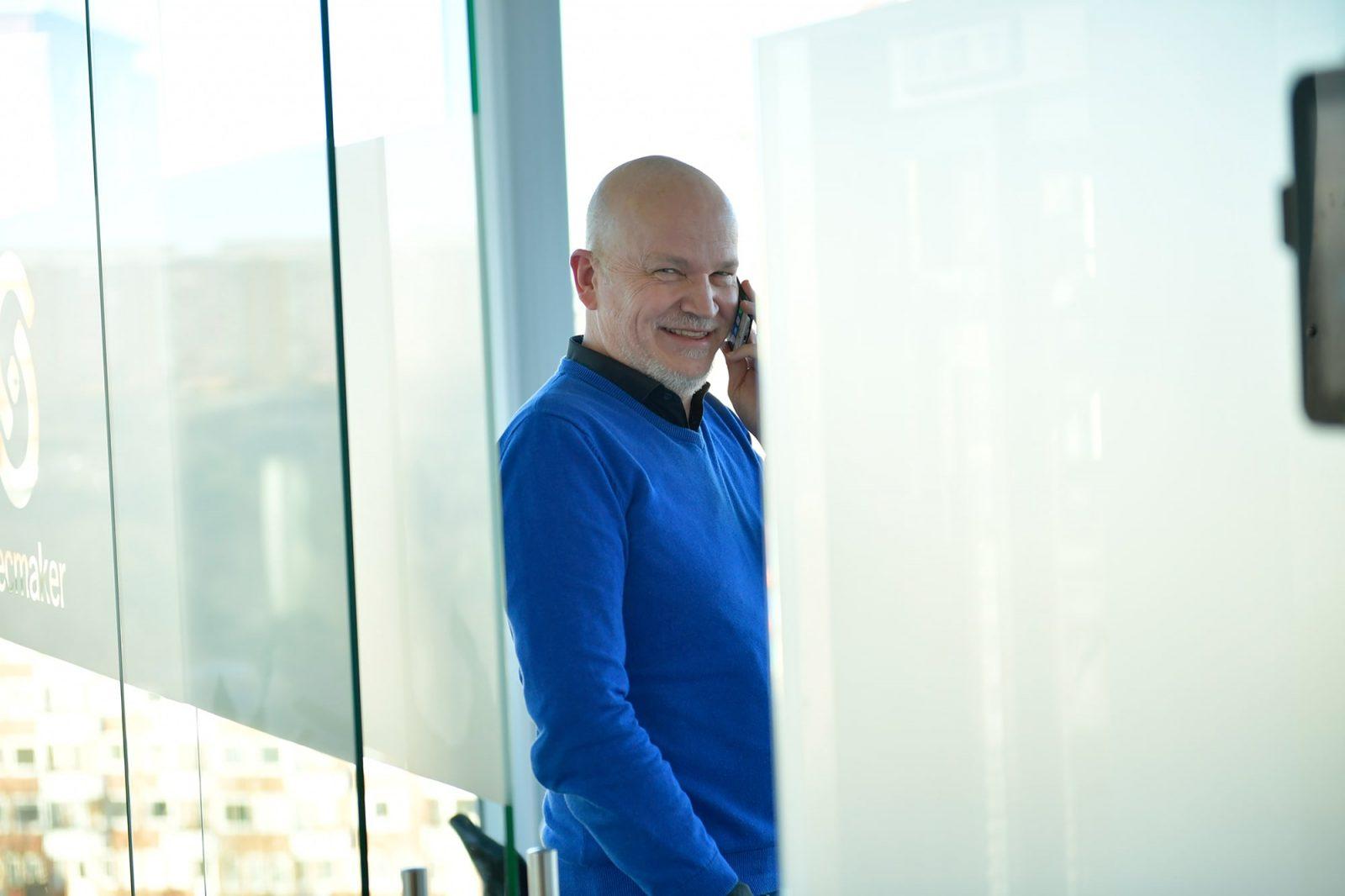 glad man i blå tröjoa pratar i telefon