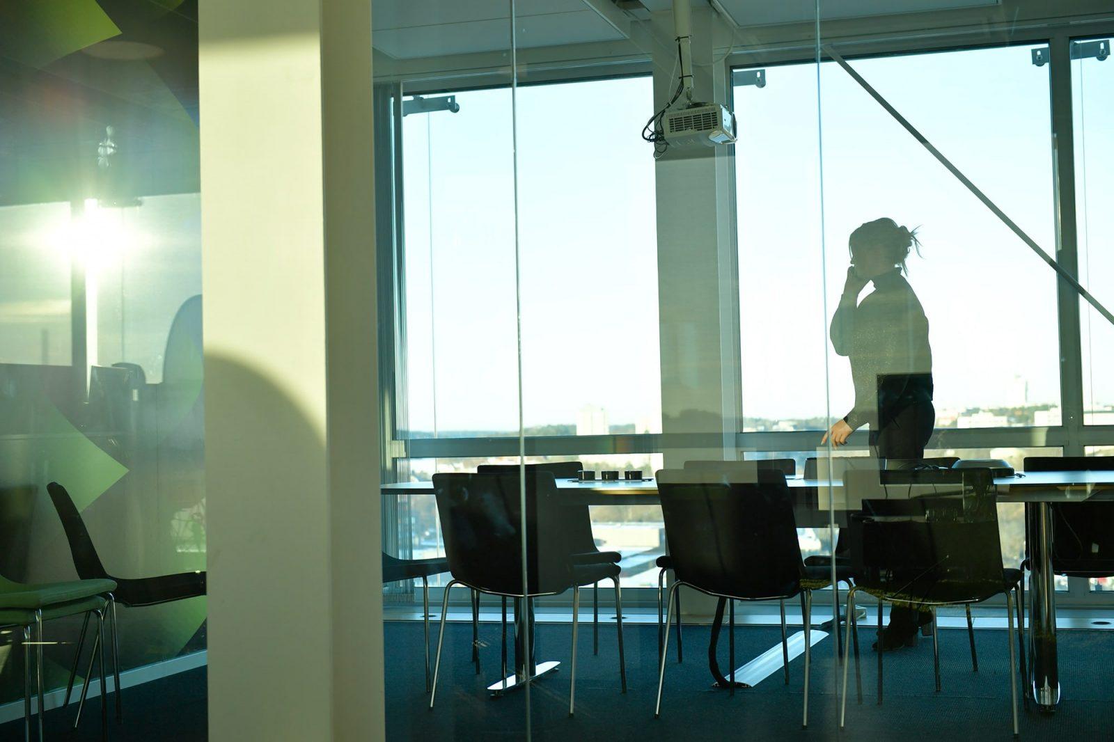 Kvinna står i konferensrum och pratar i telefon