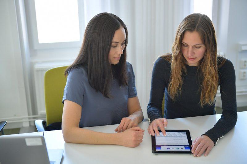 Två kvinnor tittar ner i en iPad