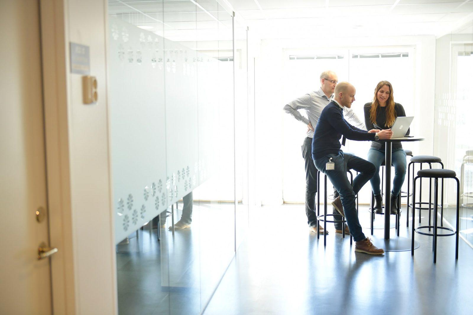 två män och en kvinna sitter vid dator