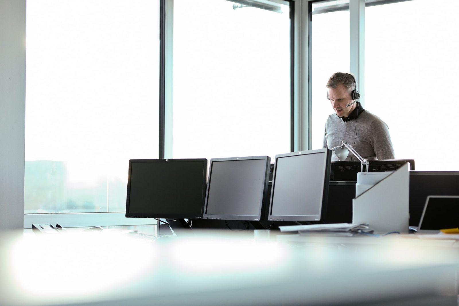 Man står med headset framför dataskärmar