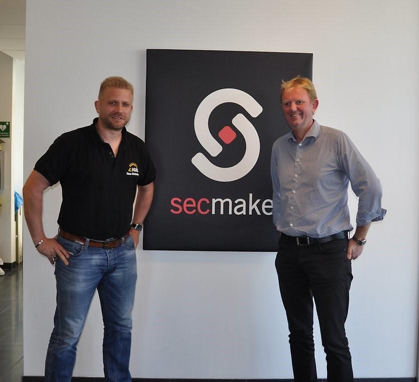 Två män står bredvid tavla med SecMaker logga